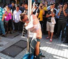 男子抢劫惹众怒,被扒光绑在柱子上示众